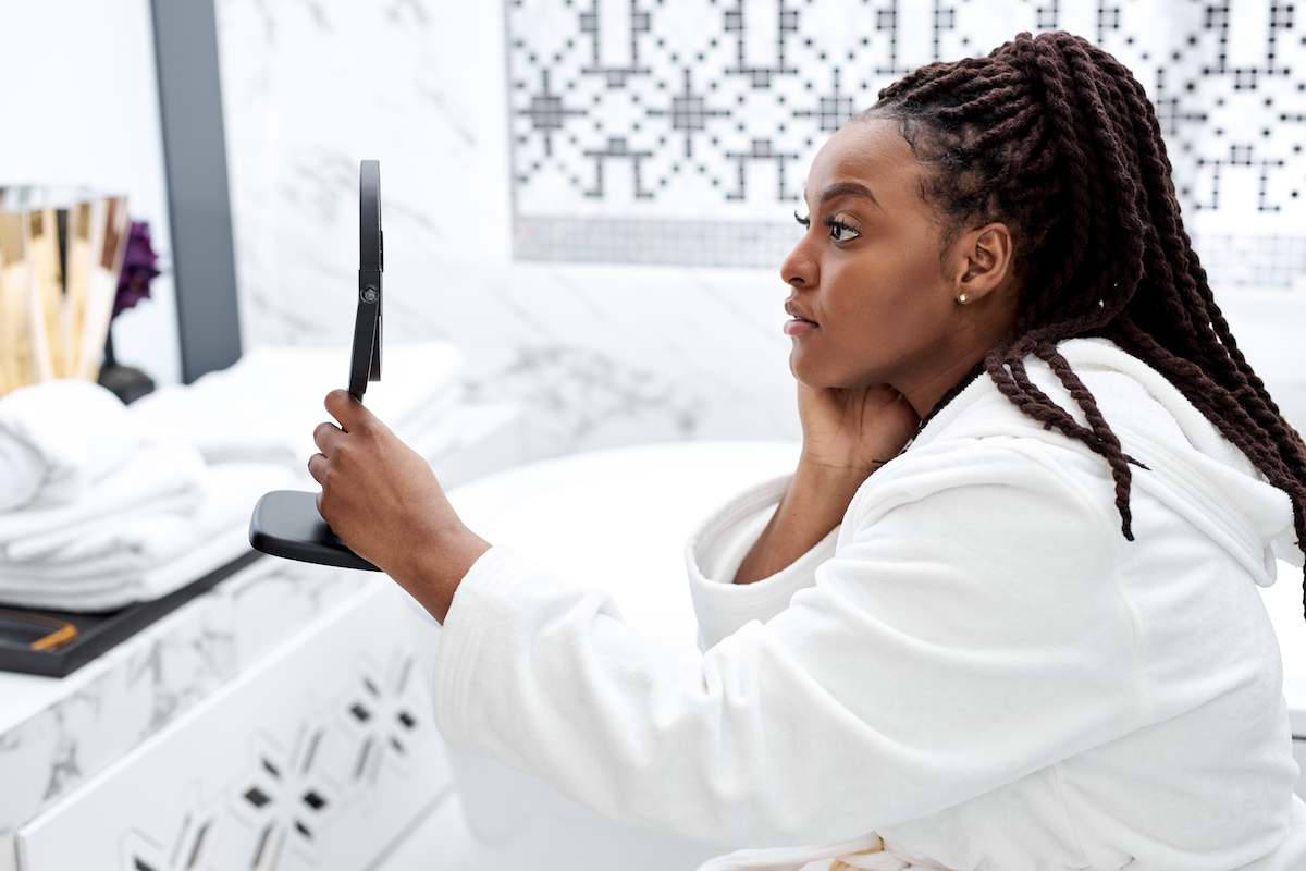 young black woman in bathrobe admiring her lash lift from The Lash Lounge