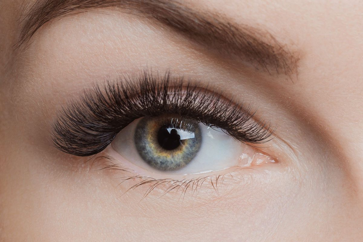 A close-up of a woman's eye and eyelash extensions