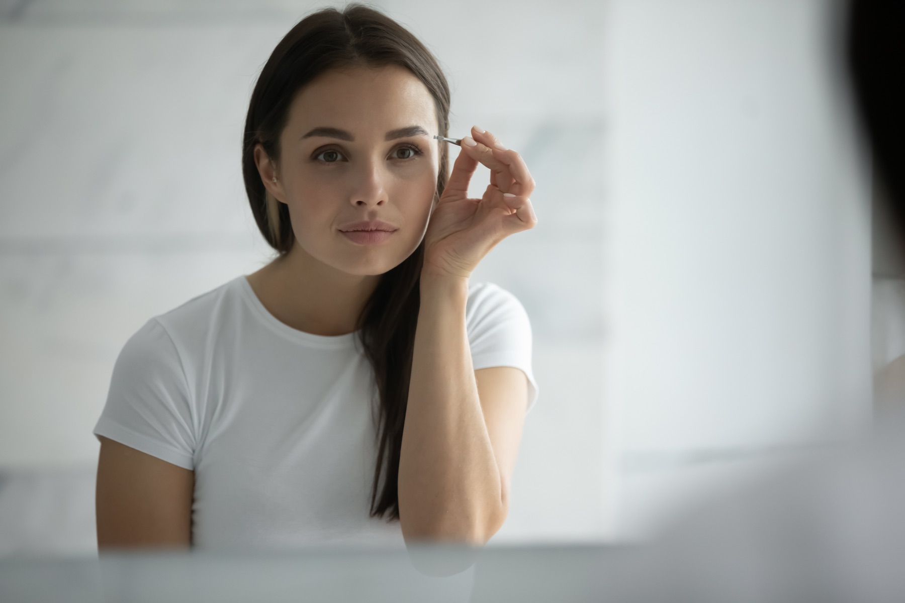 brunette white woman looking in a mirror while tweezing her eyebrows