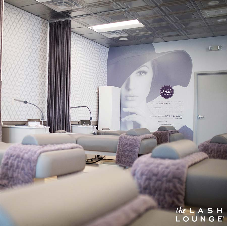 The Lash Lounge luxurious salon service area with spa beds, purple blankets, and company manifesto with empowering words for women