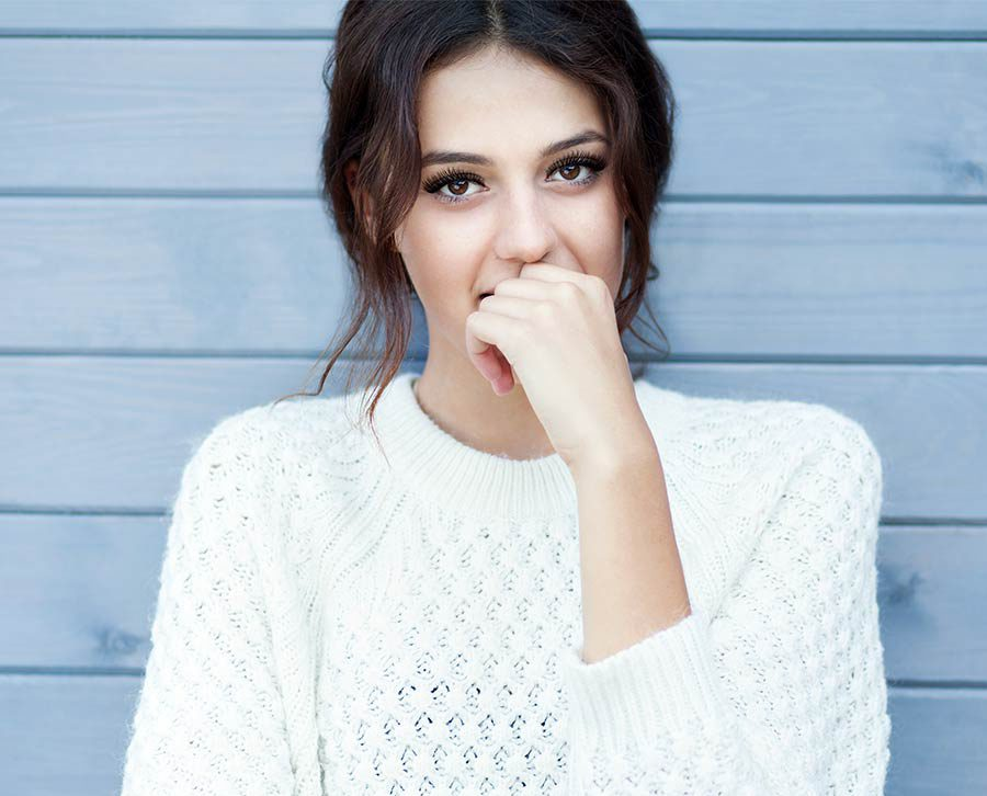 brunette with lash extensions posing in a cable knit sweater