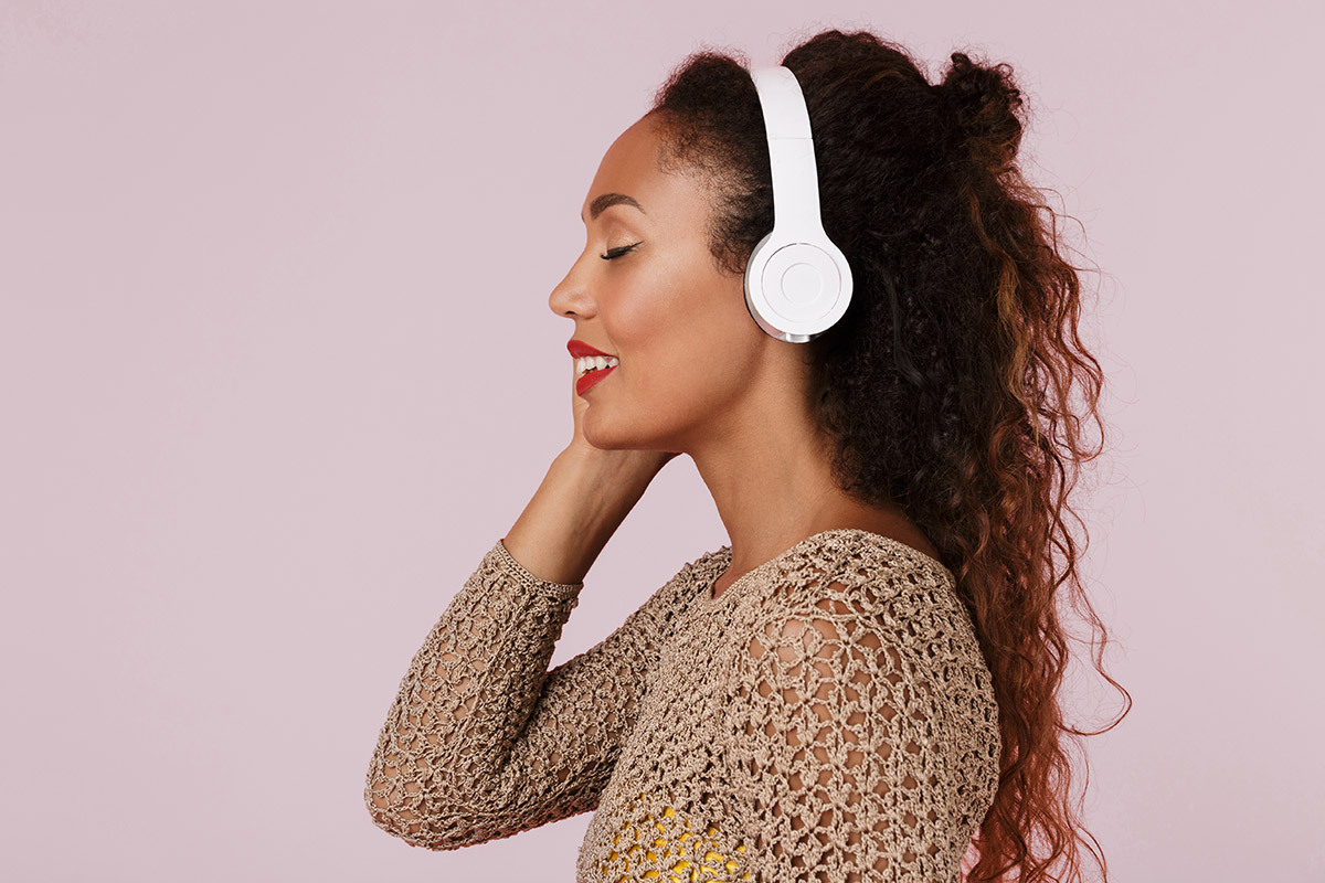 A young black woman smiling with her eyes closed listening to music with white headphones on her ears.