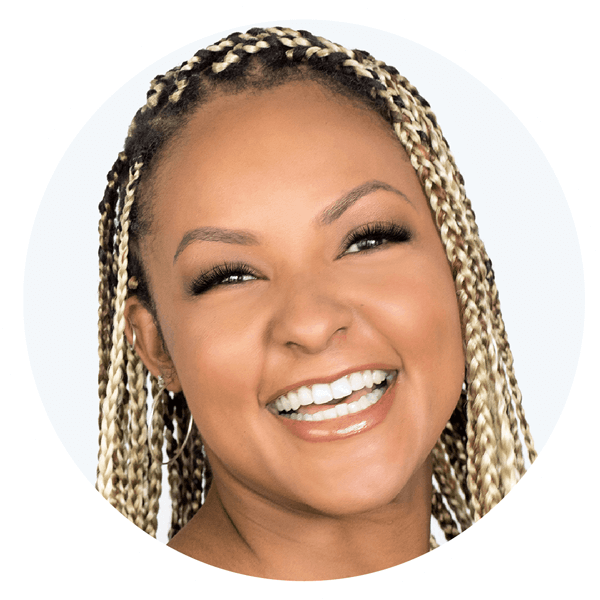 Black woman with new eyelash extensions and braids smiling big