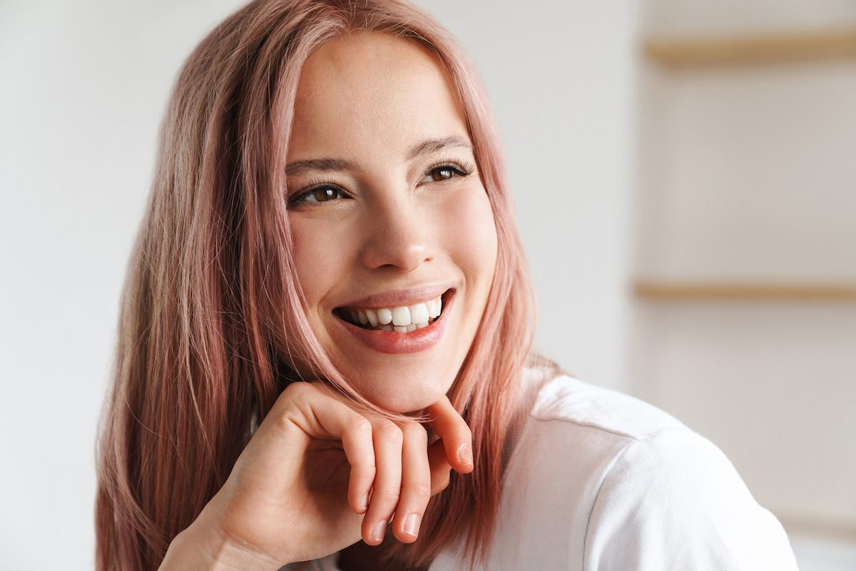 young asian woman with pink hair smiling big with new lash extensions for the new year