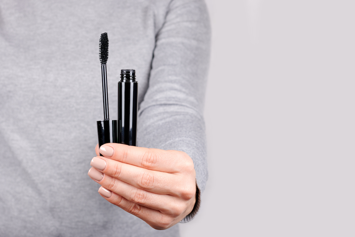 close-up of a woman's hand holding an open tube of mascara
