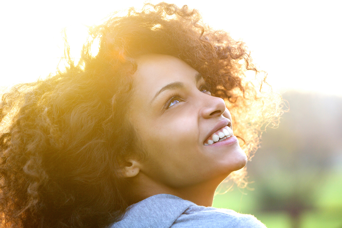 black woman with lash extensions outdoors in the sunshine