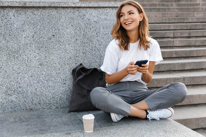 woman smiling in the city on the phone with new lash extensions