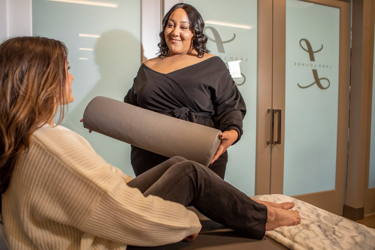 A lash technician holding a knee pillow smiles at a Lash Lounge guest.