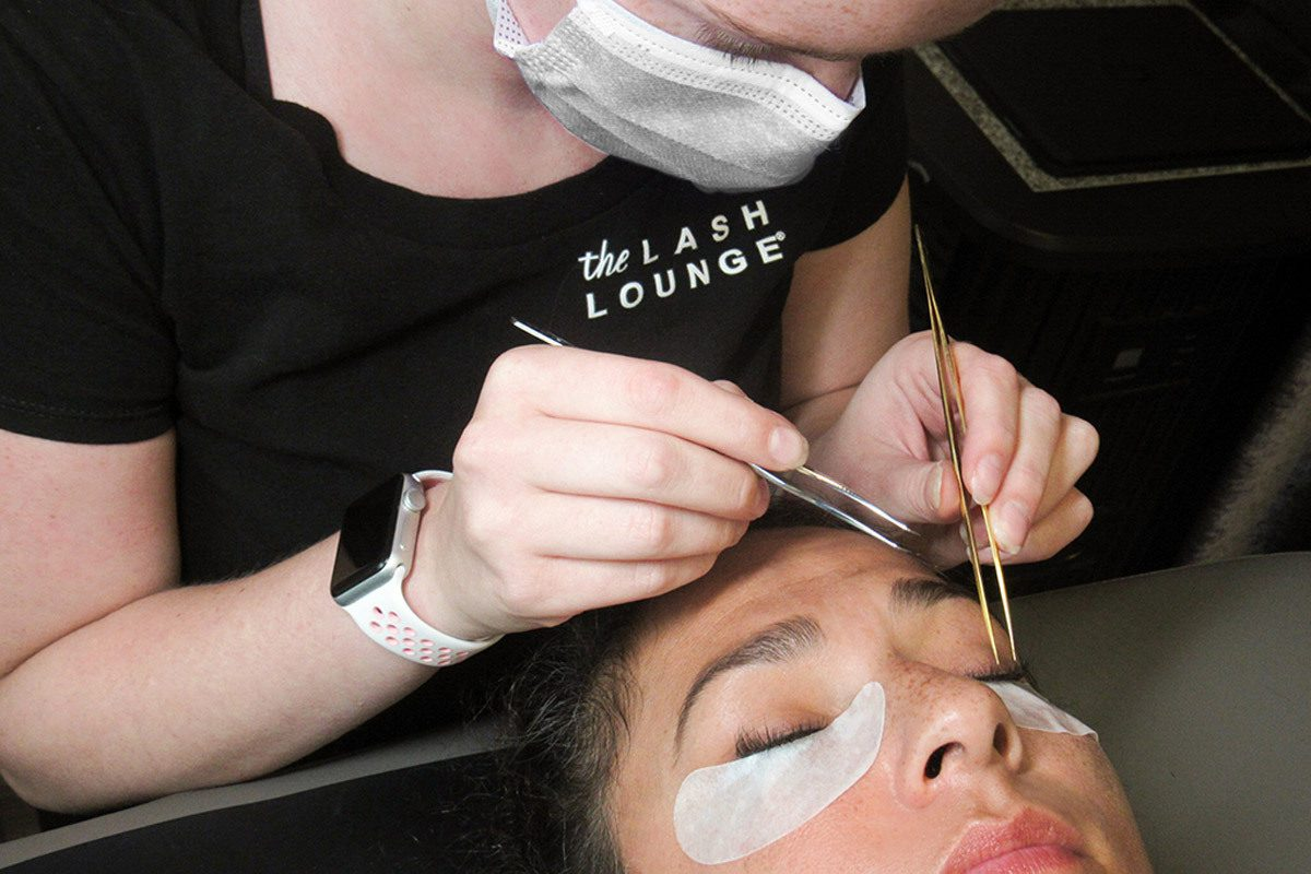 lash stylist from The Lash Lounge applying lash extensions on a guest