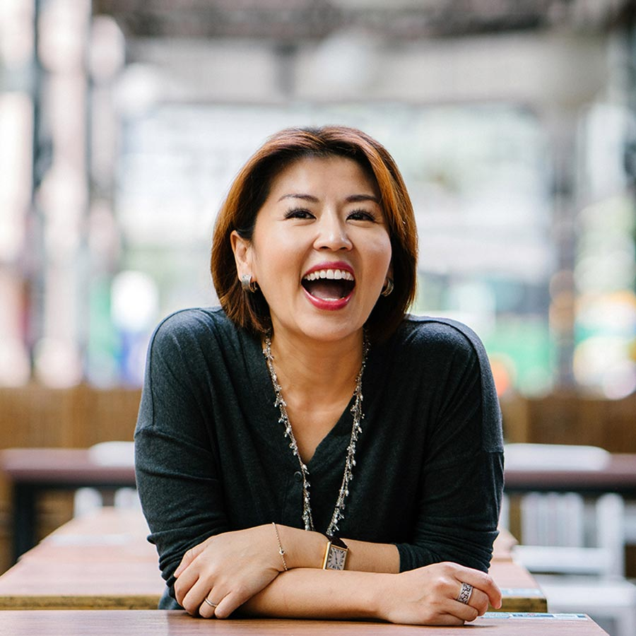 woman with lash lift smiling in a cafe