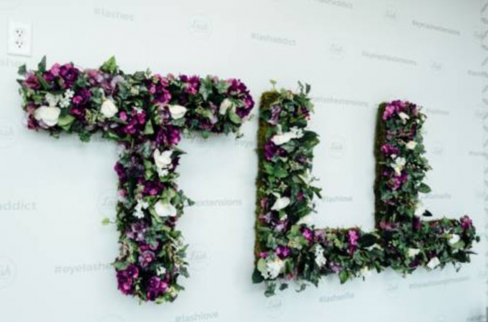 TLL spelt out in purple and white flowers hanging on the wall