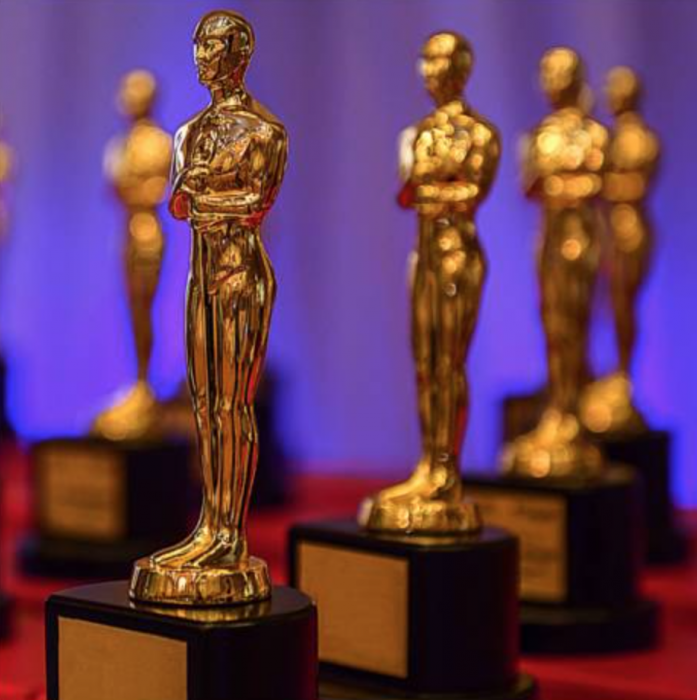 Close up of Oscar awards lined up on a red cloth
