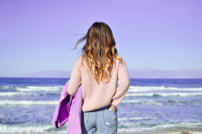 Girl from behind with curly hair holding a purple jacket looks at the ocean and sky