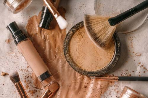 assortment of brown toned makeup products and brushes spread across a table