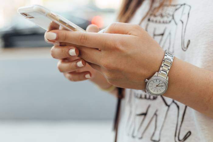 close up of a girl holing her phone wearing a white shirt and nail polish with a watch on
