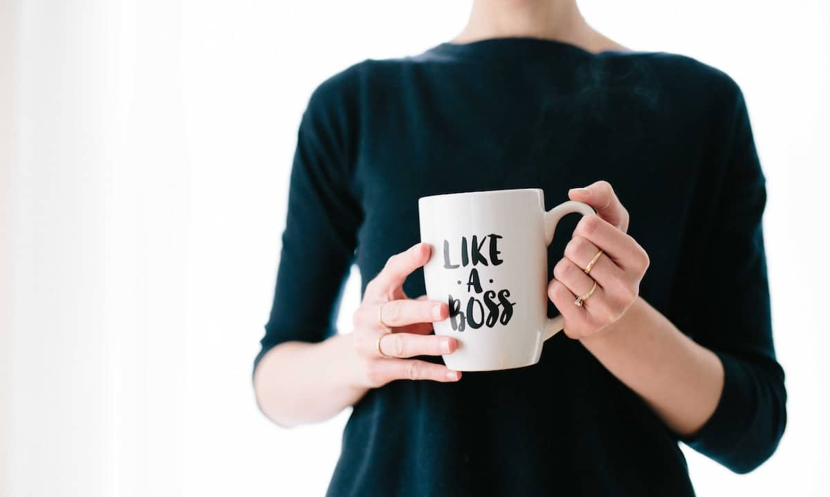 close up of woman in a black shirt holding a mug that says 'like a boss'