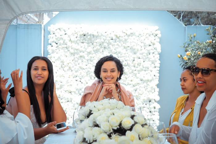 A woman smiles at the end of a table with her friends in front of a white flower wall