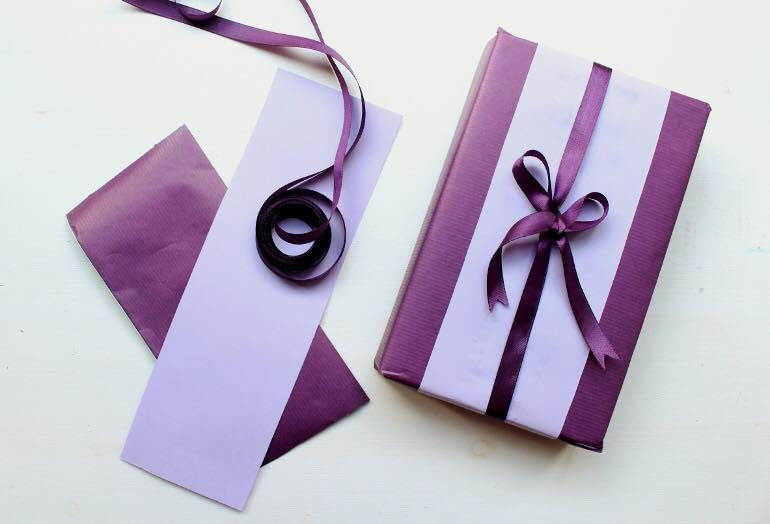 A box wrapped in light and dark purple paper and ribbon