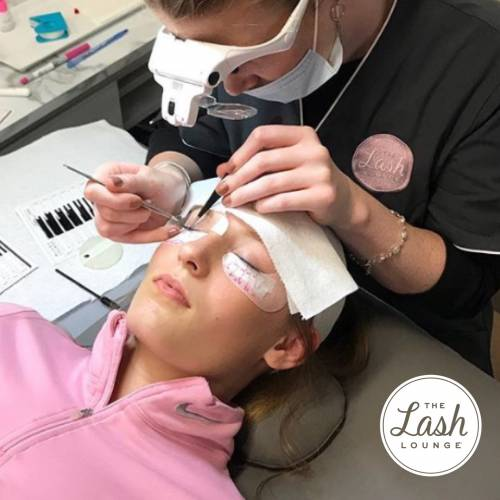 A lash stylist from The Lash Lounge putting eyelash extensions on a young woman in pink