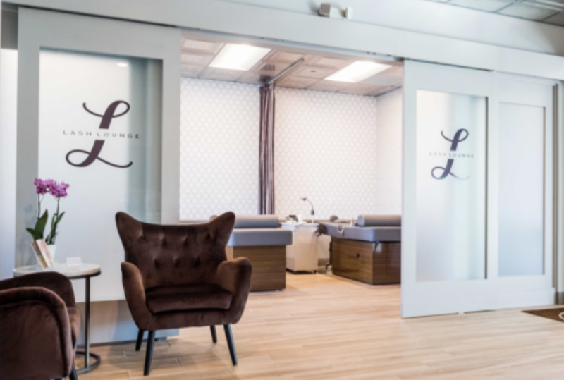The Lash Lounge waiting area with seating and doors that lead to the lash studio