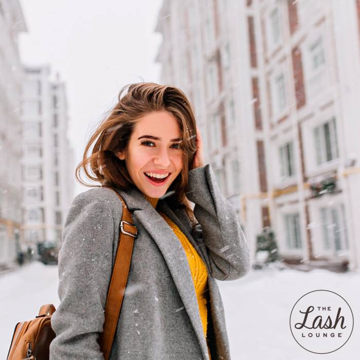 brunette girl smiles with lash extensions from The Lash Lounge in the snowy street