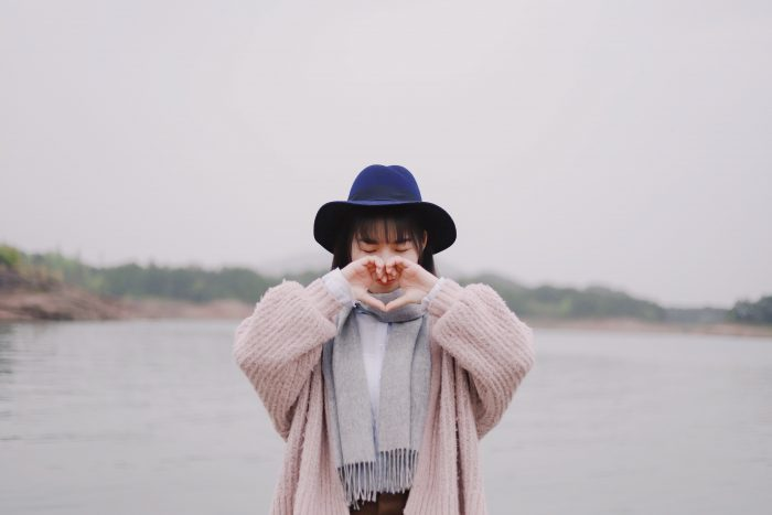 woman in a hat and scarf poses with her hands in a heart in front of a lake with trees