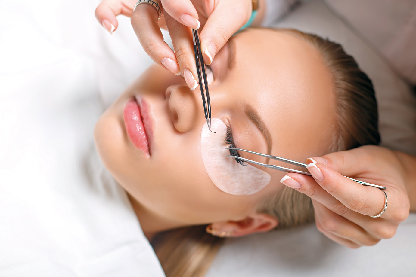 close up picture of lash extensions being applied to blonde woman at The Lash Lounge