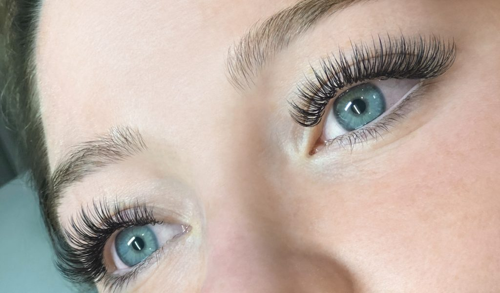full set of classic lash extensions on woman with blue eyes