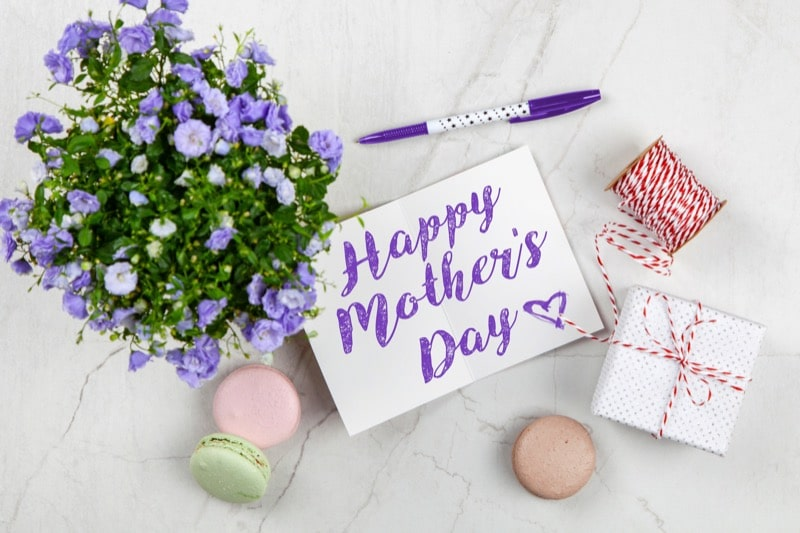 purple flowers and macaroons with 'Happy Mother's Day' written on the card
