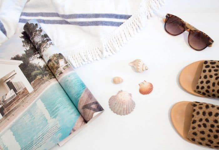 beach essentials such as sandals, magazine, sea shells, and a towel