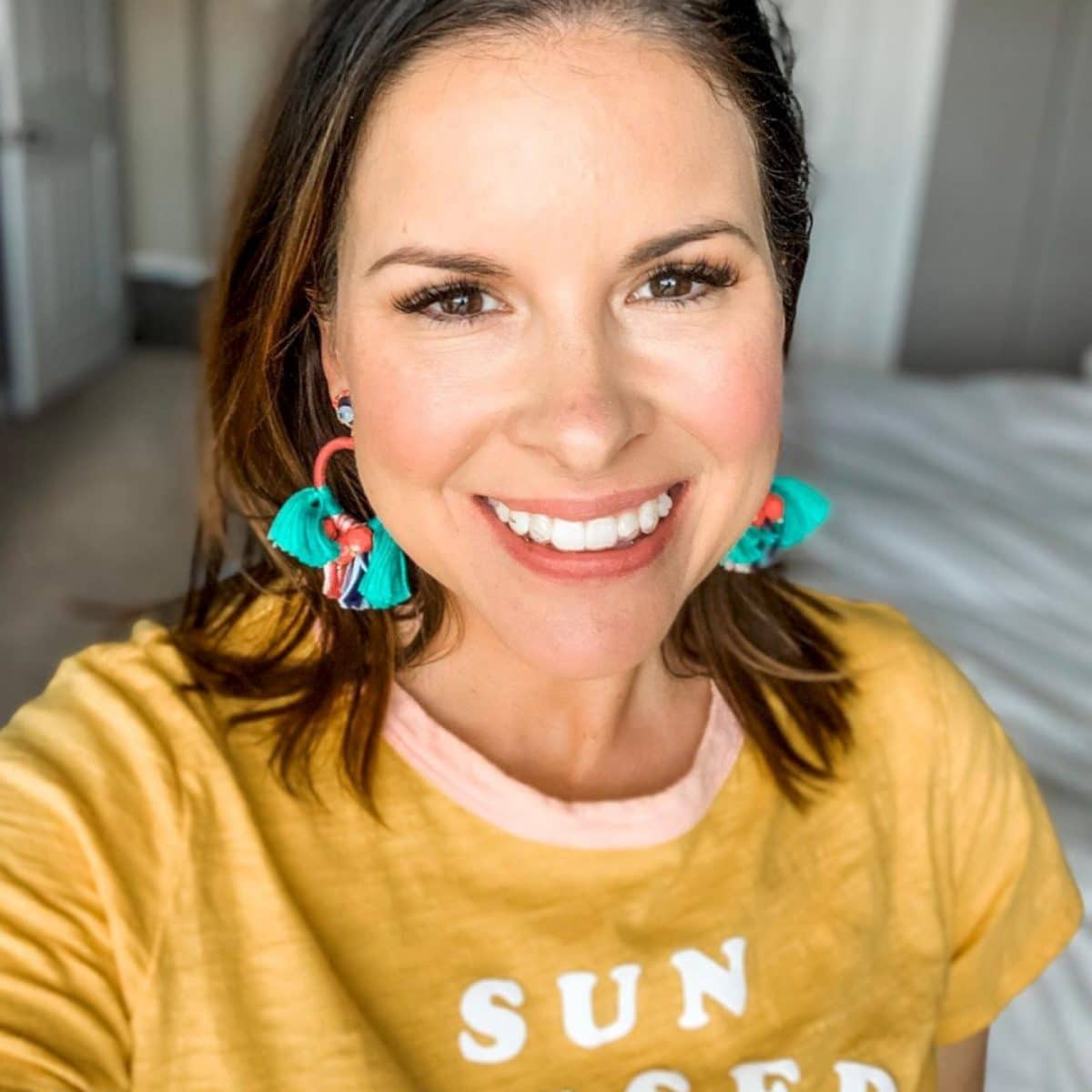 brunette woman in yellow shirt smiles with lash extensions