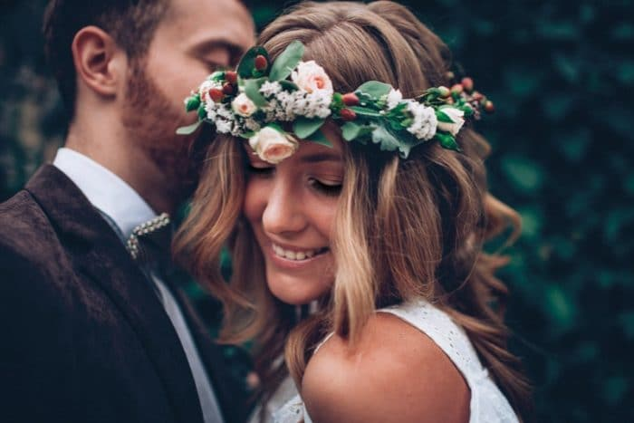 A bride with curly hair and a flower crown smiles facing a her groom