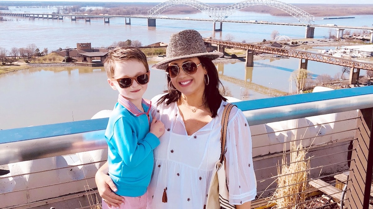 A woman and her son smiling from a balcony overlooking the water
