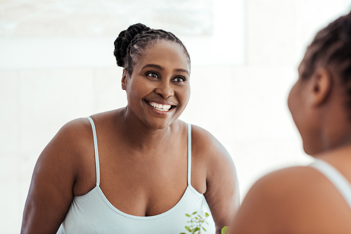 Smiling African woman looking at her reflection in a mirror
