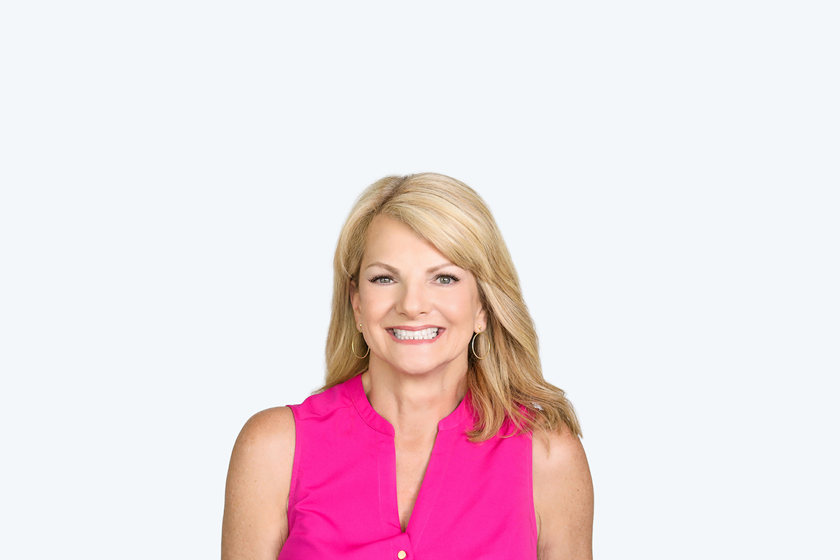 smiling blonde woman wearing pink in front of white wall