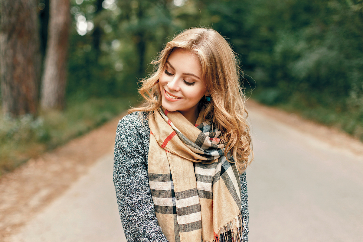 blonde woman smiles with a scarf on in the road with trees in the back