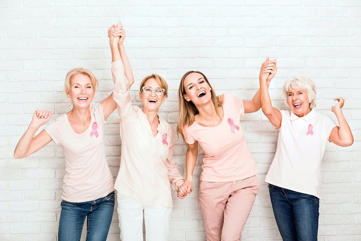 A group of women smiling and holding hands wearing breast cancer symbols in front of brick wall
