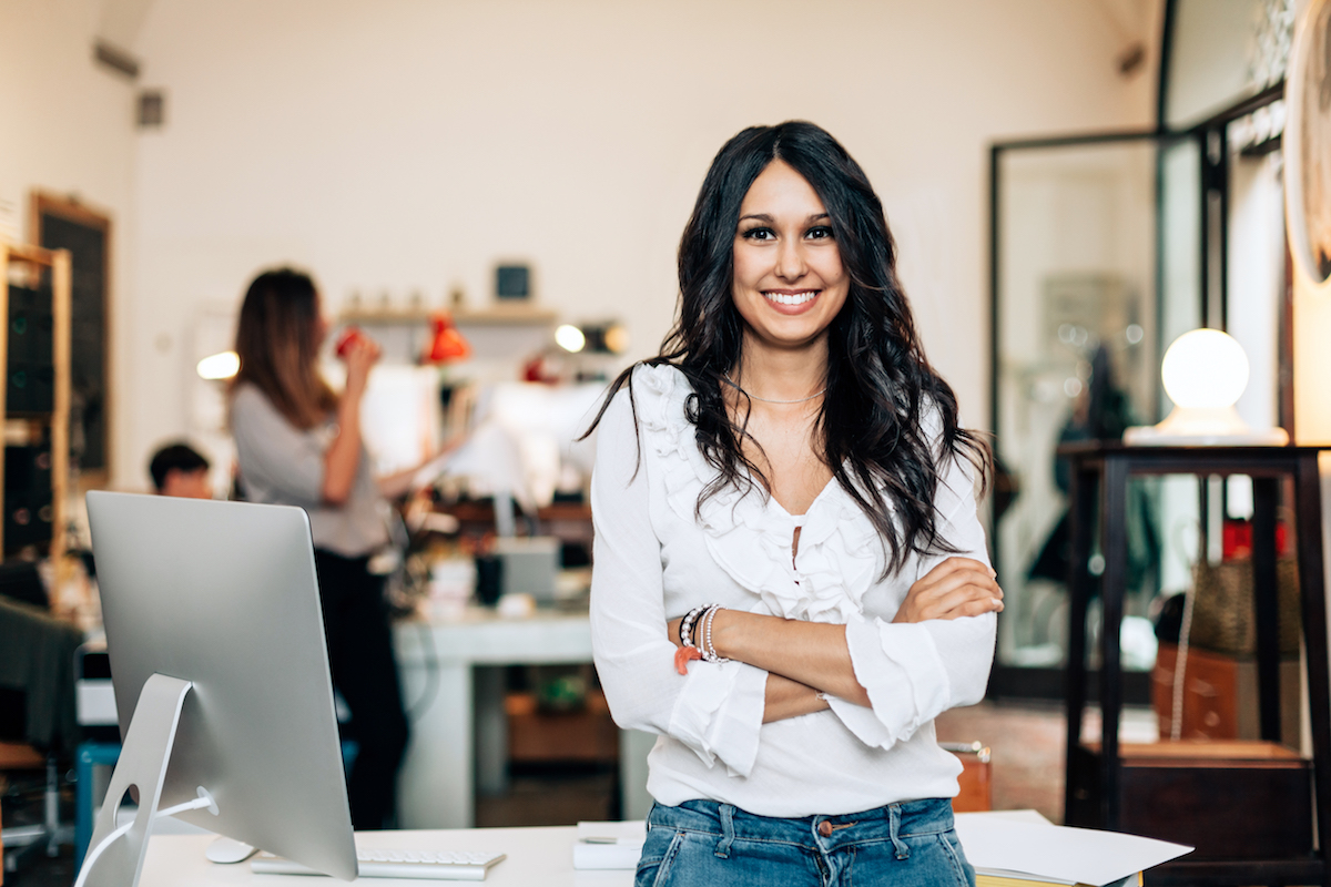 dark haired woman leans on her desk while smiling with computer and coworkers in back