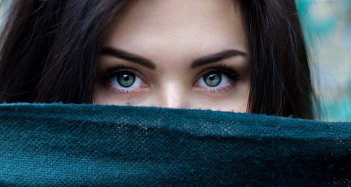 dark haired woman with green eyes staring at the camera