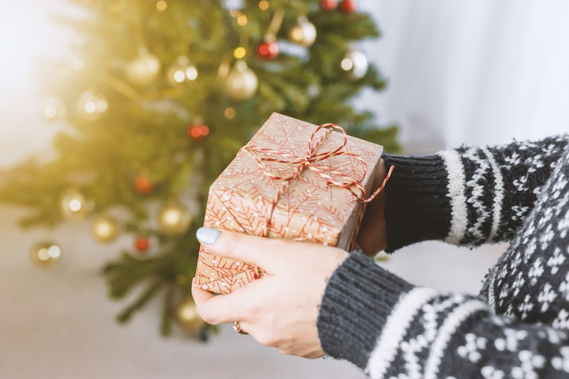 close up of woman hands holding wrapped gift in front of the Christmas tree