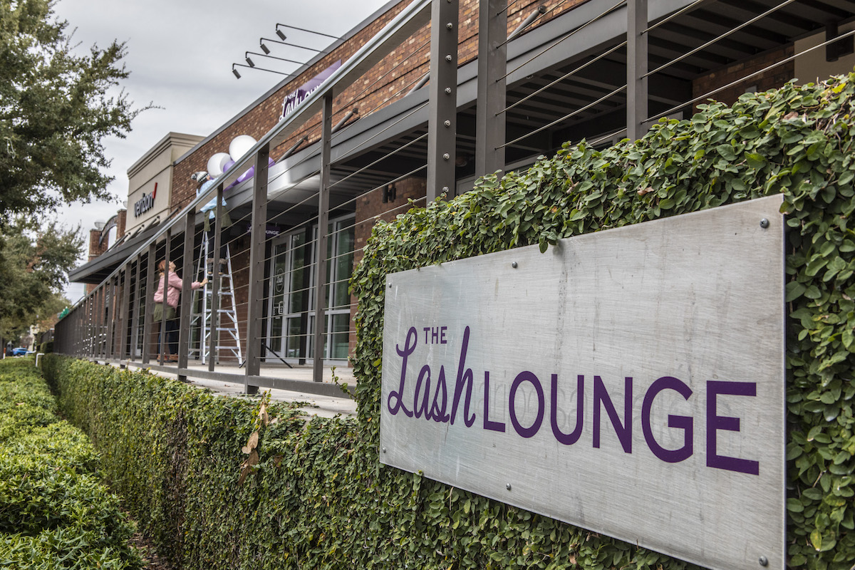The Lash Lounge sign on leafy wall outside the studio
