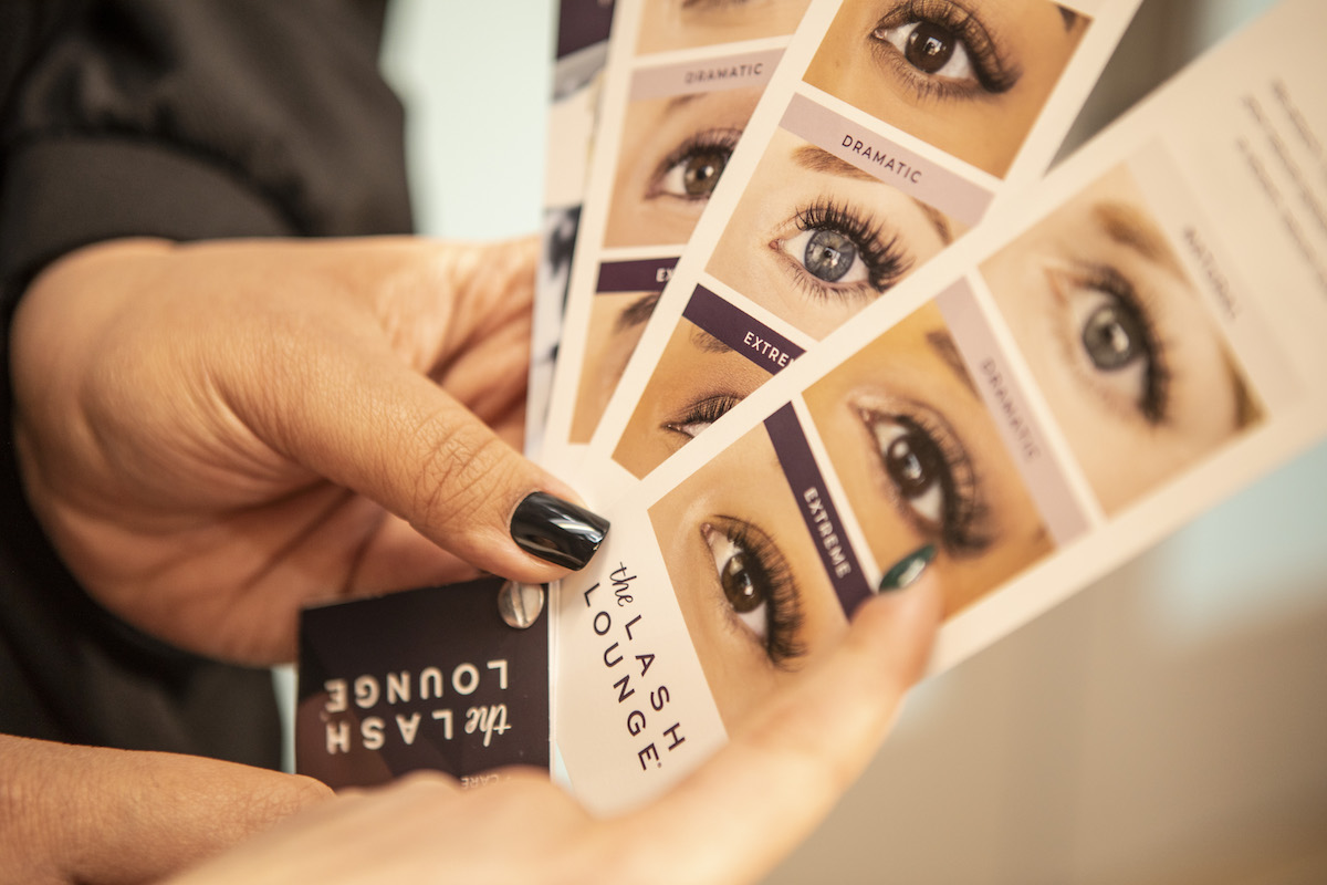 close up of hands holding swatches of lash examples from The Lash Lounge