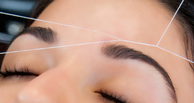 A stylist threading eyebrows on a guest at The Lash Lounge