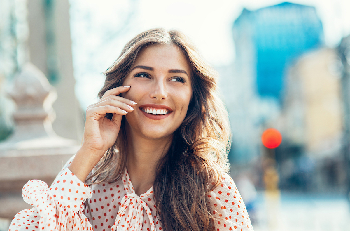 smiling young brunette woman wearing polka dots in the city