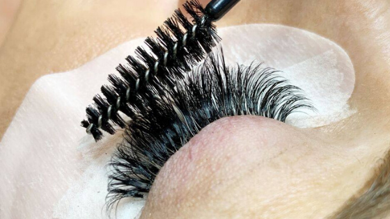Lash wand brushing lash extensions at The Lash Lounge