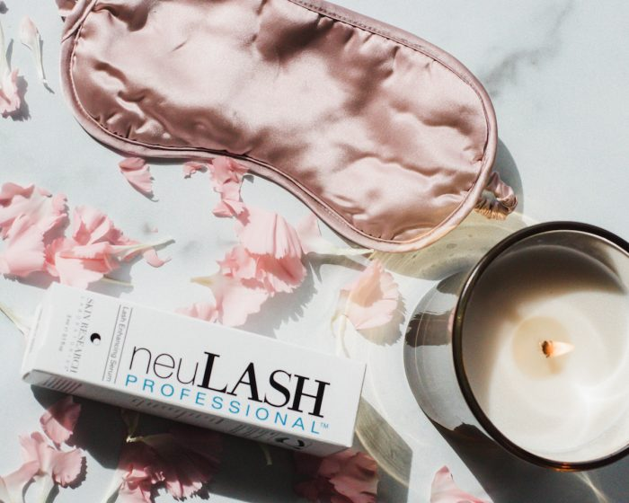 lash serum product for promoting the growth and strength of eyelashes pictured with a candle and pink satin face mask