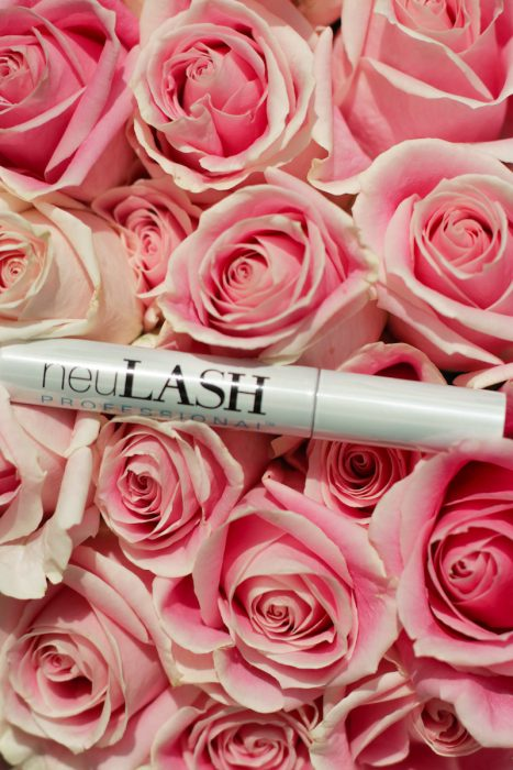 beauty product eyelash serum tube resting on a bed of lush pink roses