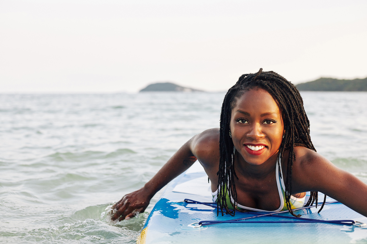 black woman in ocean swimming on surf board and smiling with eyelash extensions