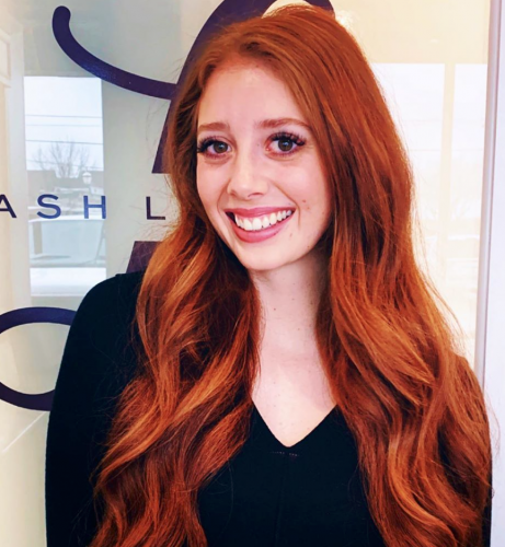 photo of an eyelash extension stylist in the salon with a beautiful smile and long red hair