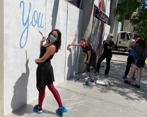 Staff member from The Lash Lounge Chicago– River North with a paint brush in hand and smiling while painting a mural on the exterior of the salon after a break in